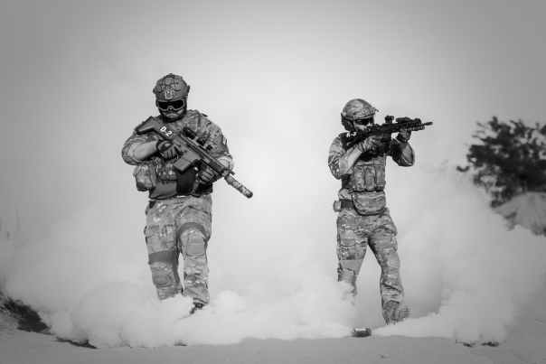 two men in military clothing with guns